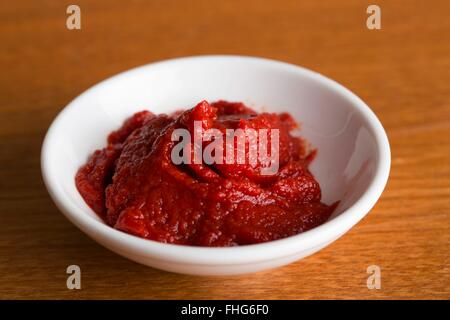 Small dish of tomato puree on a wooden kitchen table - Stock Photo