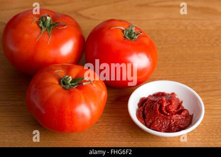 Small dish of tomato puree beside three fat beef tomatoes on a wooden table - Stock Photo