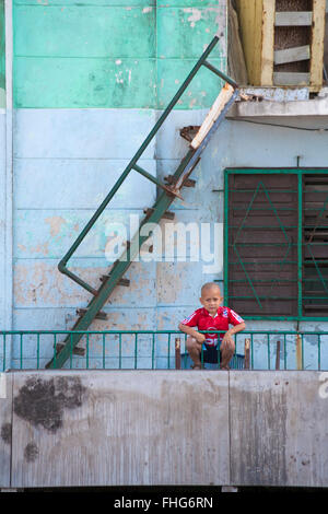 Daily life in Cuba - Cuban young boy leaning on railings at Havana, Cuba, West Indies, Caribbean, Central America - Stock Photo
