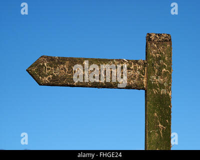 muck spattered public footpath sign in finger post design against clear bright blue sky - Stock Photo
