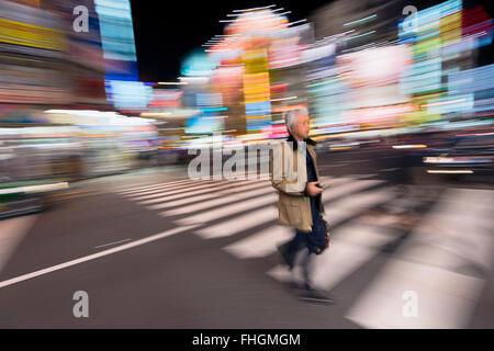 Tokyo, Japan -January 8, 2016: Abstract image of a Japanese business man in the streets of Akibahara. Akibahara - Stock Photo