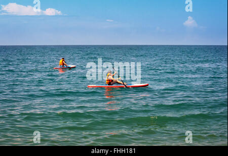 ... A boy and a woman floating on the sea in small boats and single rowing  with