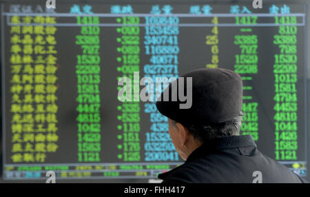 Yangzhou, China's Jiangsu Province. 25th Feb, 2016. An investor looks through stock information at a trading hall - Stock Photo