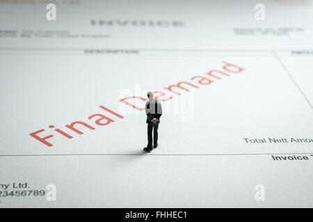 Miniature business man gloomily pondering an overdue final demand invoice a finance or debt concept - Stock Photo
