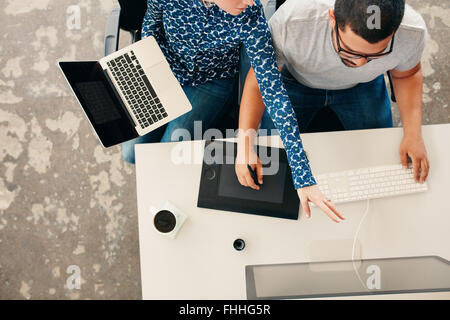 Top vie of a woman designer showing something on desktop monitor to man working graphics tablet and pc. Young graphic - Stock Photo