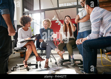 Shot of a group of young business professionals having a meeting. Diverse group of young designers smiling during - Stock Photo