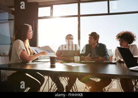 Young business woman consulting new business plans with her colleagues. Creative people discussing documents and - Stock Photo