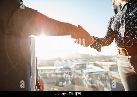 Handshake of two associates with sunlight. Male executive shaking his hand with female colleague, focus on hands. - Stock Photo