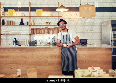 Portrait of happy young man wearing an apron and hat standing at a cafe counter holding a cup of coffee. Coffee - Stock Photo