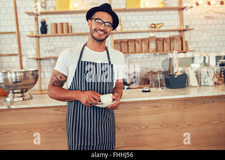 Portrait of happy young barista at work. Caucasian man wearing apron and hat standing in front of cafe counter with - Stock Photo