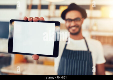 Close up portrait of a man holding up a digital tablet with a blank display. Man working in cafe showing a touch screen computer Stock Photo
