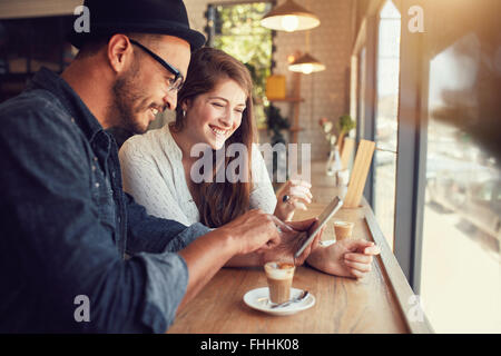 Happy couple in a coffee shop surfing internet on digital tablet. Young man and woman in a restaurant looking at - Stock Photo