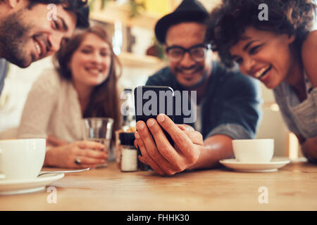 Group of friends having fun at the cafe and looking at smart phone. Man showing something to his friends sitting - Stock Photo