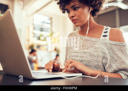 Portrait of young woman looking busy working on laptop at a cafe. African woman sitting in coffee shop using laptop. - Stock Photo