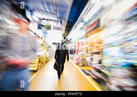 Tokyo, Japan -January 8, 2016: Abstract image of a Japanese business man in the streets of Akibahara. - Stock Photo