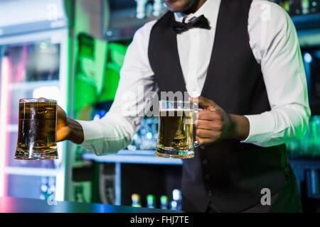 Bartender serving two glasses of beer - Stock Photo