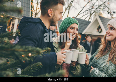 Three friends having a hot punch on the Christmas Market - Stock Photo