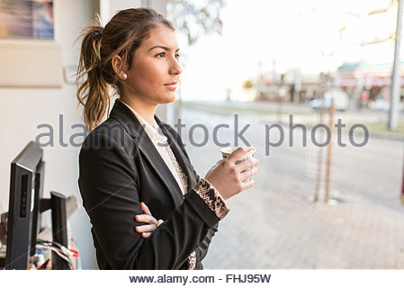 Young businesswoman looking out of window - Stock Photo