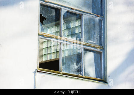 Behind a broken industrial window is yet another window with patterned glass. Focus on the glass inside the building. - Stock Photo