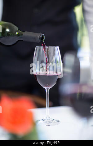 Waiter pouring a glass of red wine Stock Photo