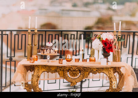 Golden wedding table in oriental style with cake and snacks. Wedding decorations close up - Stock Photo