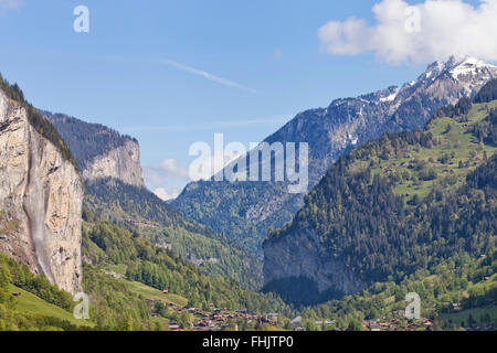 Lauterbrunnen valley in Swiss Alps, with snow mountain peaks, green alpine meadows, exposed rocks, high waterfalls - Stock Photo
