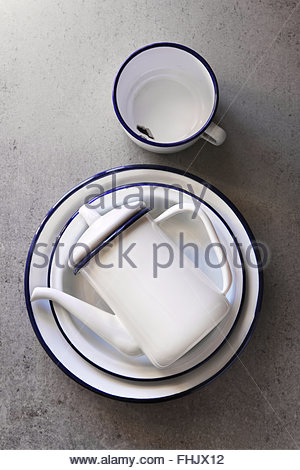 Vintage white enamel cookware, plates,mug and a teapot on a kitchen board.Top view - Stock Photo