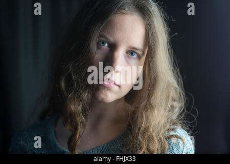 Fair-skinned woman with wavy/curly brown hair, blue eyes and serious expression in dramatic studio lighting - Stock Photo
