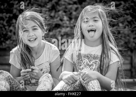 Happy Downs Syndrome girl with sister laughing and having fun - Stock Photo