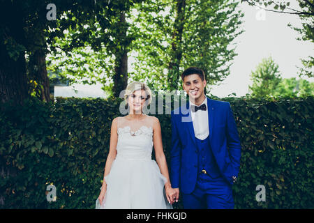 Beautiful wedding couple posing in the park - Stock Photo