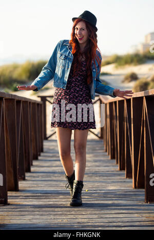 Spain, Cadiz, portrait of laughing young woman standing on boardwalk at the beach - Stock Photo