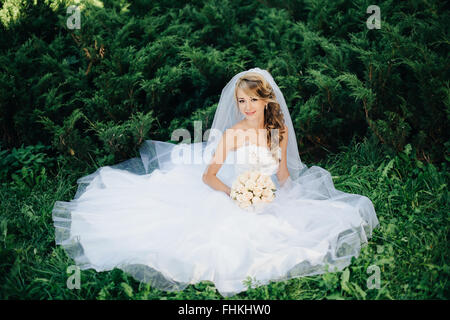 Bride sitting on green grass at park - Stock Photo