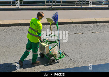 Paris, France - July 9, 2015: Street cleaner with recycling bin on the streets of Paris - Stock Photo