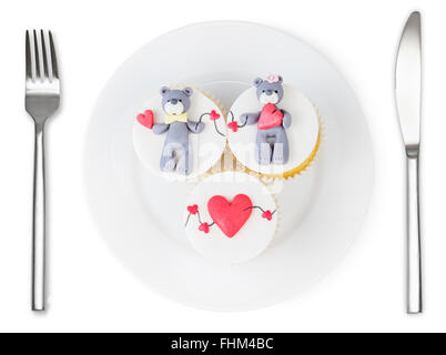 Cupcakes with teddy bear and hearts on plate isolated on white background. Love dish. - Stock Photo