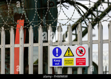 Metal fence, razor wire and danger signs on the outside of an enclosed industrial site, near Glasgow, Scotland, - Stock Photo