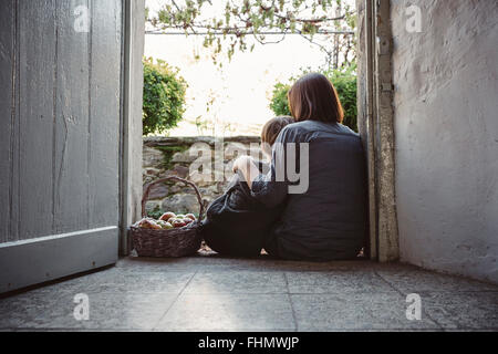 Spain, Asturias, back view of mother and son sitting at entrance of country house - Stock Photo