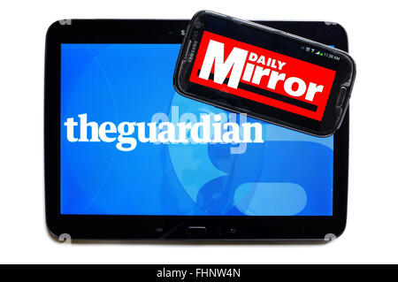 The logos of The Guardian and the Daily Mirror newspapers displayed on the screens of a tablet and a smartphone. - Stock Photo