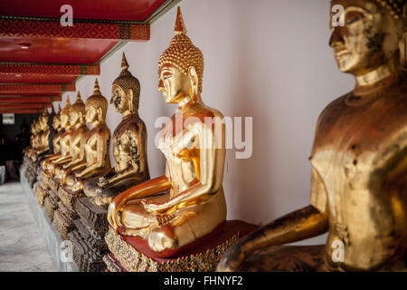 A row of seated, golden buddha statues at Wat Pho, a famous temple in Bangkok, Thailand - Stock Photo