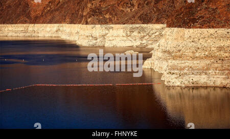The shoreline of Lake Mead showing a low water line at the reservoir at Hoover Dam - Stock Photo