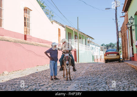 An old man on a donkey talks to his friend on a street in Trinidad, Cuba - Stock Photo