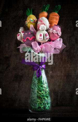 Easter vase with cake pops on wooden background - Stock Photo