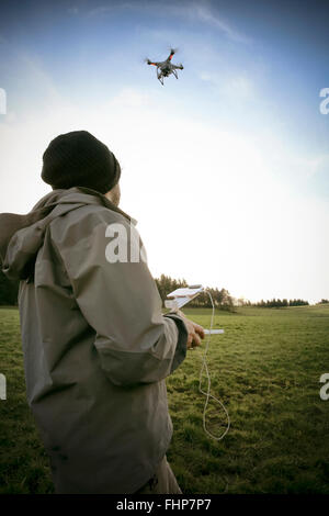 Man on a meadow flying drone - Stock Photo