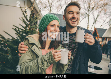 Couple having a hot punch on the Christmas Market - Stock Photo