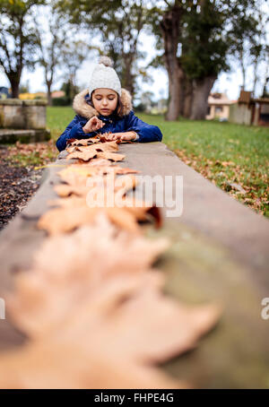 Portrait of little girl playing with autumn leaves in the park - Stock Photo
