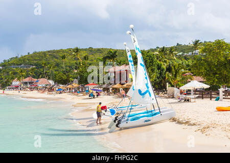 Panoramic view of Dickenson Bay, north Antigua, with parasols, sun loungers and Sandals sailing boats on the beach - Stock Photo