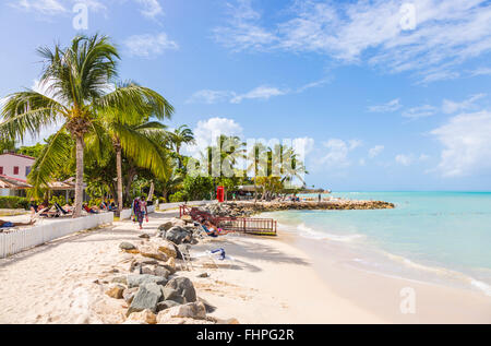 Dickenson Bay beach in north Antigua with blue sky and turquoise sea on a sunny day, Antigua and Barbuda, West Indies - Stock Photo