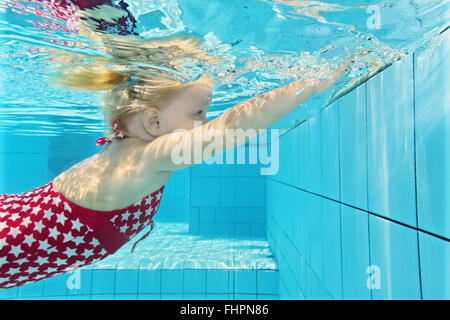 Child swimming lesson - girl learning to dive underwater in pool. - Stock Photo