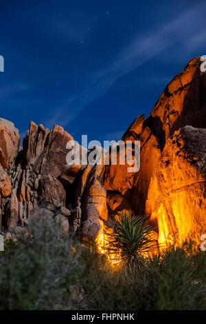JOSHUA TREE, CA – FEBRUARY 22: Campers fire light on the rocks in Joshua Tree, California February 22, 2016. - Stock Photo