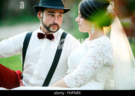 Stylish bride and groom sit on grass in rays of setting sunlight. Newlyweds couple. - Stock Photo