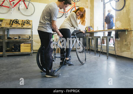 Salesman advising client in a custom-made bicycle store - Stock Photo